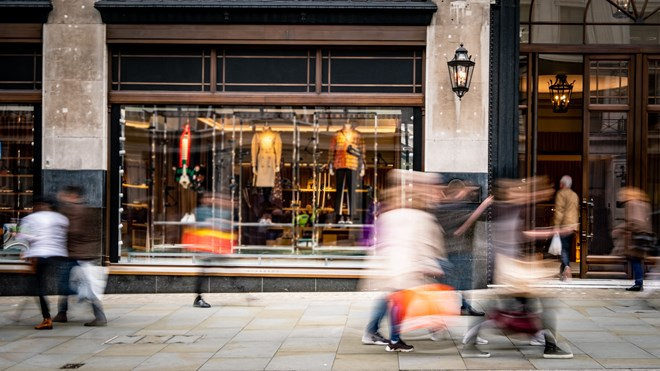 Shop front image with blurred people walking past