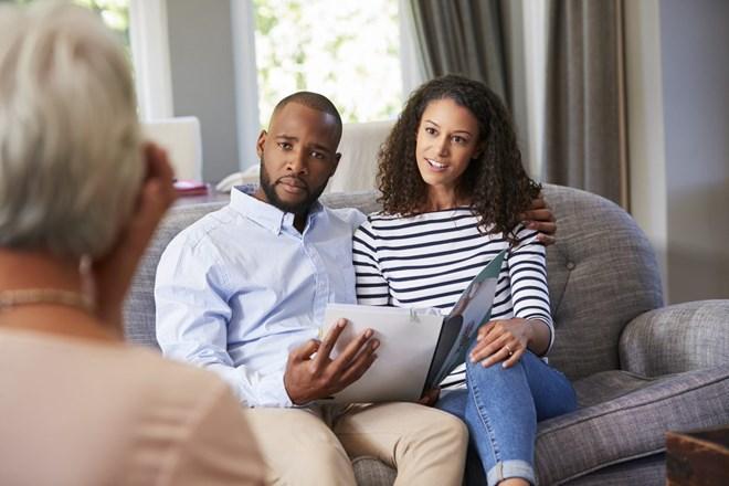 Couple sat on sofa talking to therapist
